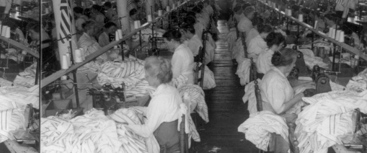 Photograph of a sewing room in a shirt factory in Troy, New York, which would have resembled the tight working conditions of the Triangle shirtwaist factory workers.