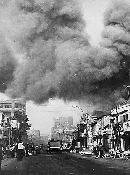 Black smoke covers areas of Saigon, and fire trucks rush to the scenes of fires set during attacks by the Viet Cong during the festive Tet holiday period in 1968.